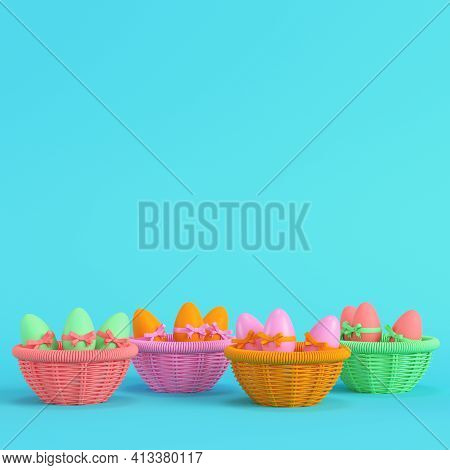 Colorful Easter Eggs With Bow In A Wicker Basket On Bright Blue Background In Pastel Colors. Minimal