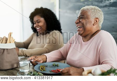 Happy Black Mother And Daughter Having Fun Eating Healthy Lunch At Home