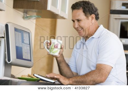 Man In Kitchen With Computer And Coffee Smiling