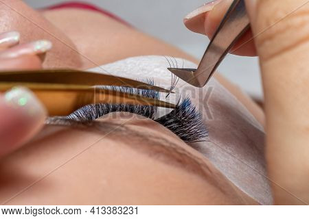 Treatment of Eyelash Extension with blue colors. Lashes. Woman Eyes with Long Eyelashes in diferent color.