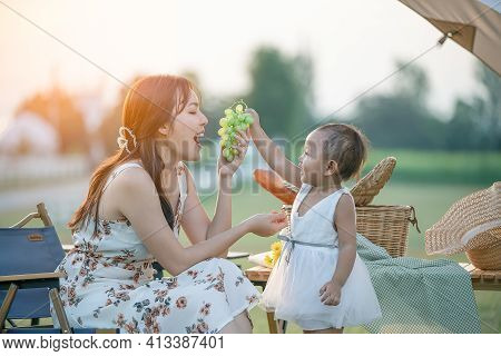 Excited Infant Daughter Girl Looking How Your Mother Eat Grape During Picnic. Hungry Woman Funny Pos