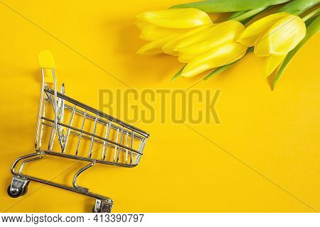 Yellow Tulips On A Solid Color Background And Shopping Cart. Online Shopping In Spring And Summer, B