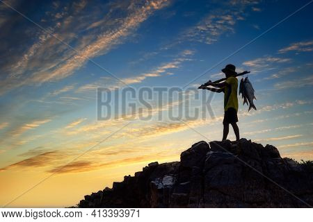 Silhouette Fisherman Carrying Fish On A Rock At Sunset. Fisherman In Mekong River, Thailand.