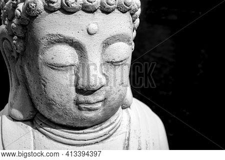Face Of Buddha Statue White Isolated On Black Background. Founder Of Buddhism. Black And White Photo