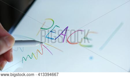 Woman Hand View While Digital Writing Peace Word On A Graphic Tablet