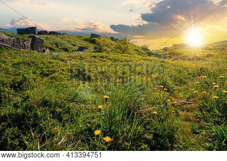 Mountain Meadow At Sunset. Cloud Rolling Above The Hill With Rocks Among The Grass In Evening Light.