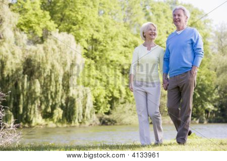 Couples Walking Outdoors At Park By Lake Smiling