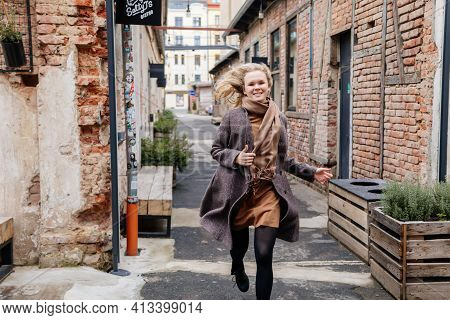 Happy Beautiful Young Woman Runs Along The Street, Girl In Black Tights, Beige Dress And Gray Coat,