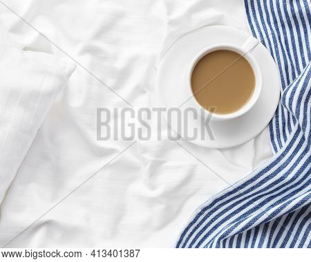 Cup Of Coffee With Milk On The Bed With White Linens And Blue Bedspread. Morning Coffee Concept.