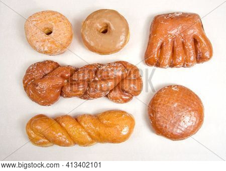 Flat Lay Top View Of Variety Of Specialty Donuts. Glazed Twists, Cinnamon Twist, Jelly Filled, Bear