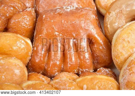 Close Up On Variety Of Donuts Arranged On Parchment Paper Clustered Together. Bear Claw In The Cente