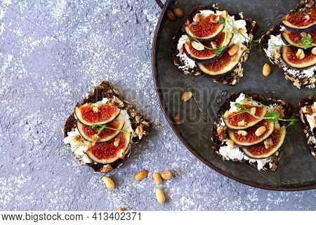 Canape, Crostini Or Bruschettas With Fresh Figs, Bread, Cream Cheese, Honey On Metal Tray And Slate