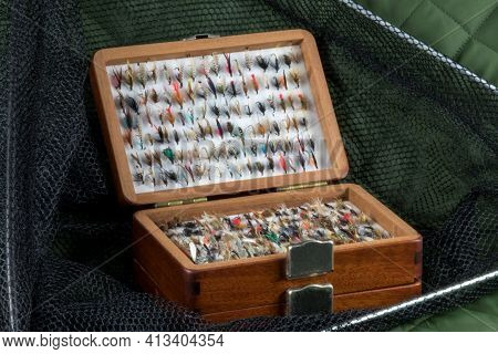 Old Wooden Fly Box And Trout Flies With Landing Net On An Outdoor Coat