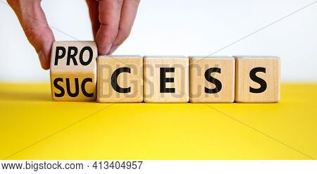 Success Process Symbol. Businessman Turns Wooden Cubes And Changes The Word 'success' To 'process'.