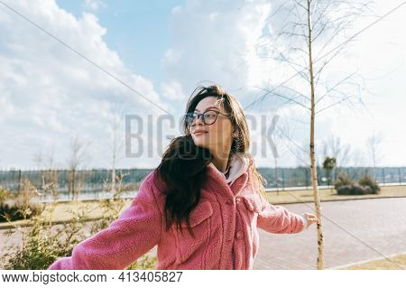 Portrait Of Young Cheerful Caucasian Woman Walking In The Park And Having Fun, Enjoying Spring Weath