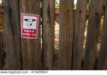 Cukurbag, Turkey - 15 October, 2019: Beware of dog in Turkish language Warning sign with image of cute puppy muzzle on old wooden fence