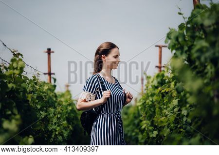 Beautiful Young Girl With Small Backpack And Positive Expression On Her Face. She Is Dressed In Dres