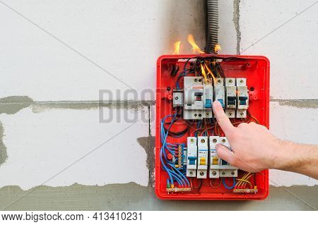 Male Hand Turns Off Burning Switchboard From Overload Or Short Circuit On Wall. Circuit Breakers On