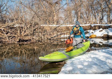 senior male paddler is lauching an inflatable whitewater kayak on a small river - Poudre River in Fort Collins, Colorado, winter or early spring scenery
