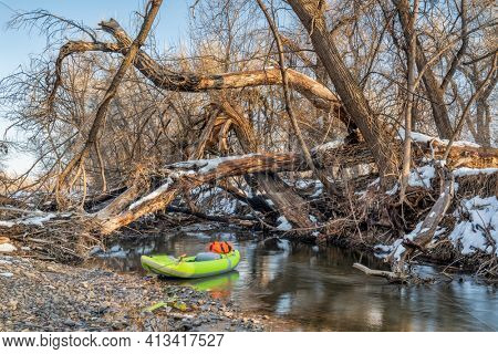 inflatable whitewater kayak above river log jam - Poudre River in Fort Collins, Colorado, winter or early spring scenery