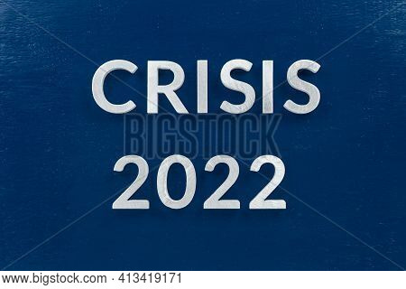 The Words Crisis 2022 Laid With Luminium Letters On Blue Painted Board