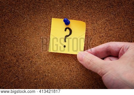 A Man Taking A Pinned Paper Note With A Question Mark From A Cork Board. Close Up.