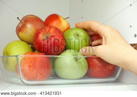 A Woman Taking A Green Apple Out Of A Pile Of Apples That Are In A Glass Tray That Is In A Kitchen C