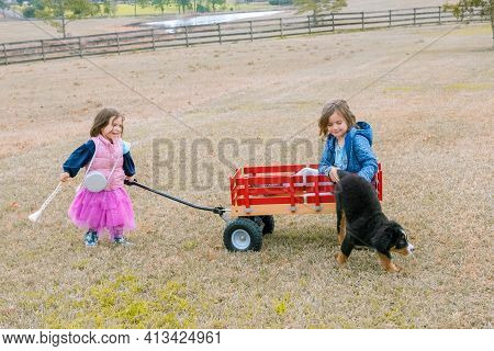 Cute Girl Pulling Her Sister And Puppy Dog In A Red Wagon. Little Sisters Having Fun On Backyard.