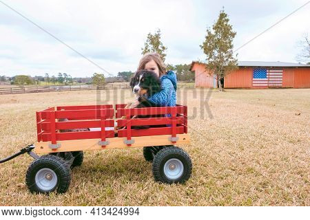 Cute Girl Having Fun With Her Puppy Dog. Happy Child And Pet In Red Wagon.