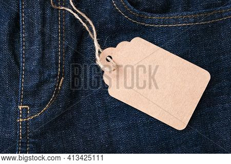 A Craft Paper Tag Label With Copy Space On Dark Blue Jeans Background With Fore Pocket, Denim Fashio