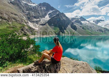 Sporty Girl Sitting Enjoying Beautiful View Of Mountain Lake Near Kaprun,austria.quiet Relaxation Ou