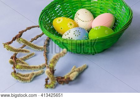 Easter Egg As A Decoration In A Green Basket. Decorated Easter Eggs On The Easter Table. The Backgro