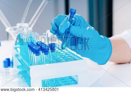 Development Of New Vaccines.hand Of Scientist Holding Flask With Lab Glasware And Test Tubes In Chem