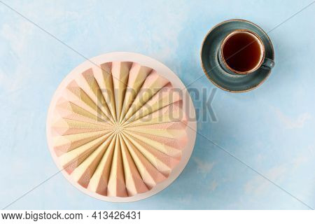 Top View Of A Traditional French Mousse Cake Pina Colada With A Cup Of Tea On The Table