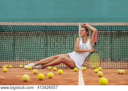 Relaxing After Tennis Training. Young Beautiful Girl In White Uniform And Sporty Cap Lying On A Tenn
