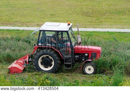 Tractor With Trailer Mowing Grass.ride-on Lawnmower.tractor Mows Lawn Grass In The City.