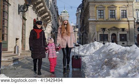 Two Young Smiling Women Travelers With Adoption Child Girl Walking With Suitcase, Looking At Famous