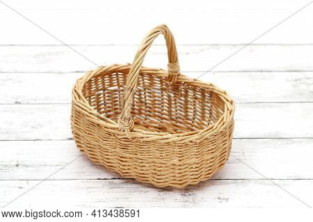 Empty Rattan Basket On A White Wooden Table