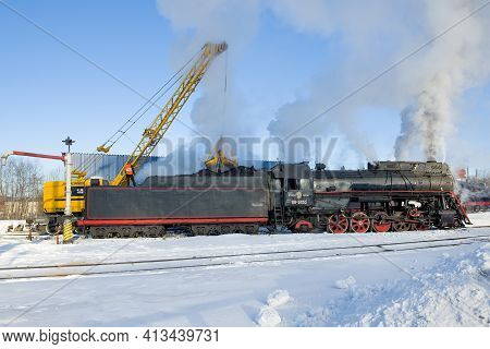 Sortavala, Russia - March 10, 2021: Coal Loading Of The Old Soviet Steam Locomotive Lv-0522 On The R