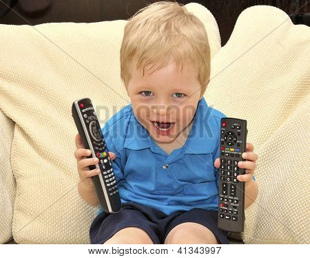 Cute Kid Watching Tv, Sitting In A Very Comfortable And Soft Chair, With A Remote Control