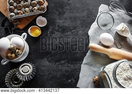 Ingredients For Baking, Flour, Eggs, Forms And Utensils On A Black Background With Place For Text