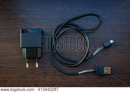 Old Mobile Charger Wire For Smartphone With Bare Wires On Wooden Background