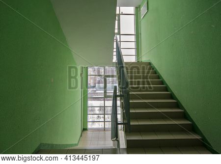 Corridor In A Residential Building. Wide-angle View Of A Modern Corridor With Doors Against A Green