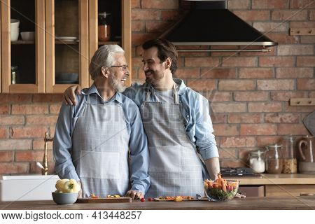 Happy Elderly Father And Adult Son Cooking In Kitchen
