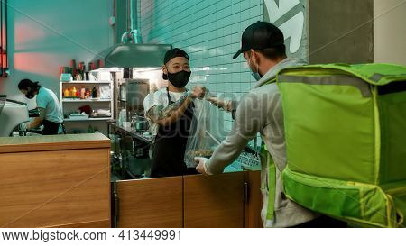 Young Man With A Mask On His Face Giving A Bag Of Food. Food Delivery Man With A Bag On His Shoulder