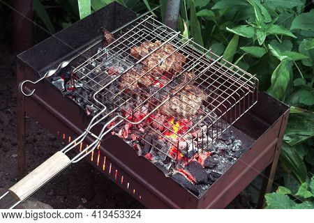 Marinated Meat In Grilling Basket And On Flat Skewer Of Steel, Cooked On Red-hot Charcoal In A Charg