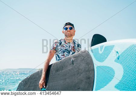 Smiling Blonde Surfer Man In Blue Sunglasses And Cap Carrying The Surfing Board On The Bright Sunny