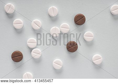 White And Brown Pills Lie On A Sheet Of Gray Paper. Close Up. Light Background Or Backdrop On The Th