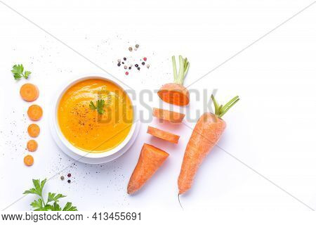 Bowl Of Carrot Soup  With Carrot Pieces Isolated On White Background With Copy Space. Top View.
