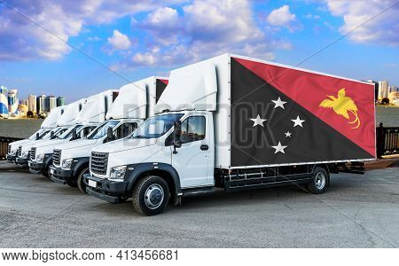 Papua New Guinea Flag On The Back Of Five New White Trucks Against The Backdrop Of The River And The